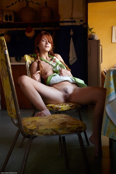Naked redhead girl in apron in the kitchen